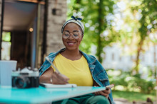 Happy Afro-american Woman Making Notes In Notepad