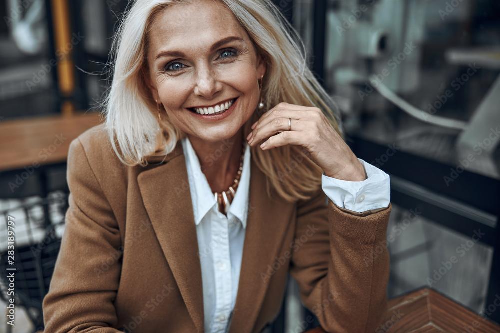 Fototapeta Mature woman outdoors expressing happiness stock photo