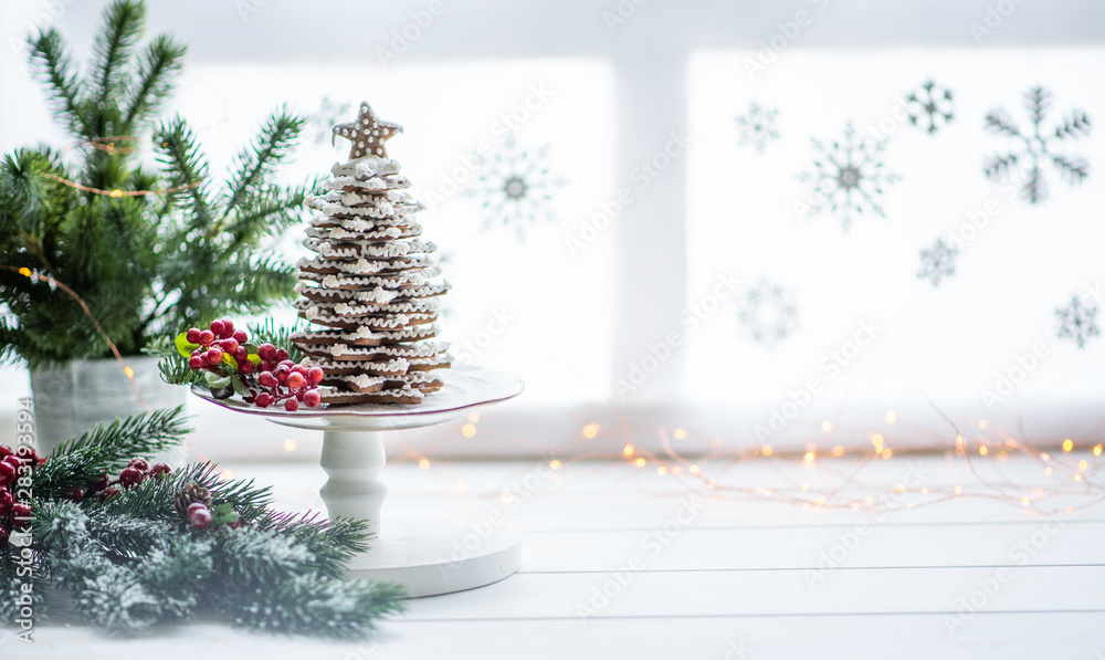 Fototapety, obrazy: The handmade eatable gingerbread and New Year Tree with decoration. Gingerbread over defocused magic light winter window. Wonderful holiday mood. Copy space for your text.