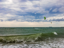 Two Kitesurfers Ride On The Waves Of A Stormy Sea In Cloudy Windy Weather On A Sunny Summer Day.