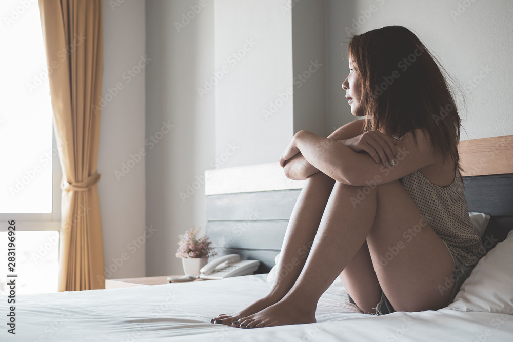 Fototapety, obrazy: Young asian woman in sad sitting on a bed