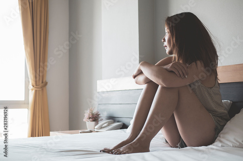 fototapeta na lodówkę Young asian woman in sad sitting on a bed