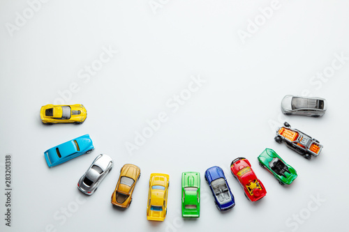 Obraz Many colored little toy cars on a gray background. - fototapety do salonu