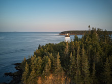 Aerial Drone Image Of The Owls Head Lighthouse Surrounded By Pristine Forest On The Cliffs Overlooking The Entrance To Owls Head Harbor On The Maine Coast At Sunset