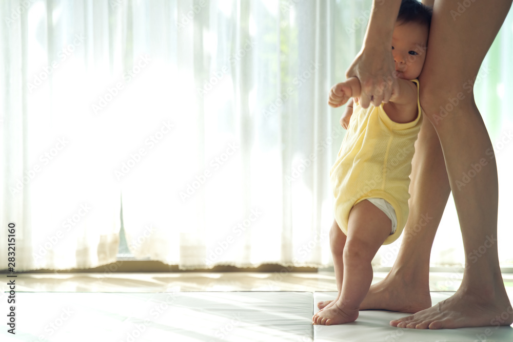 Fototapety, obrazy: Asian baby taking first steps walk forward on the soft mat. Happy little baby learning to walk with mother help at home. Mother teaching how to walk gently. Baby growth and development concept.