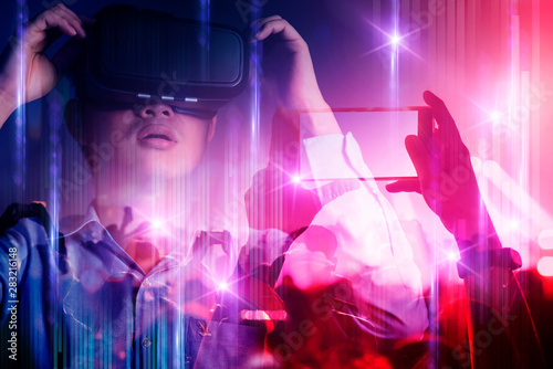 Obraz young asian officer man playing and hand touch effect of magic from Virtual reality with in live concert music performance virtual reality atmosphere event - fototapety do salonu