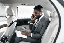 Afro Businessman Arranging His Affairs In The Car