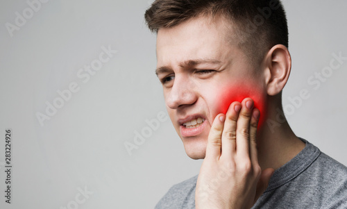 Stampa su Tela Frustrated young man touching his tooth and frowning face