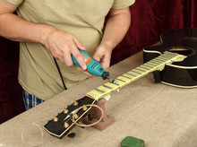Guitar Repair And Service - Worker Polishing Acoustic Guitar Neck Frets Dremel And Paste GOI