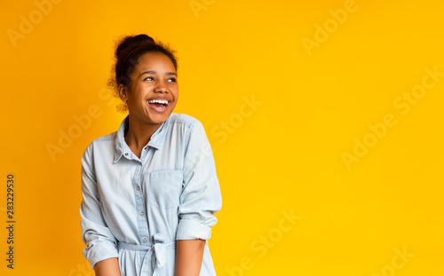 Obraz Excited black teen looking upwards standing against yellow studio background - fototapety do salonu