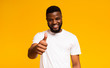 Happy guy showing thumb up and smiling over yellow background