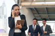 Asian business women using mobile phone and tablets with blurred soft of business group are taling about plan work and information To be successfull on job, to teamwork concept.
