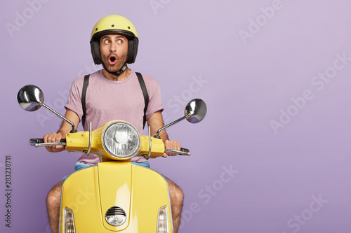 Fotografie, Obraz Isolated shot of thoughtful shocked driver drives motorbike, wears protective headgear, forgets about something important, has wonderful trip alone
