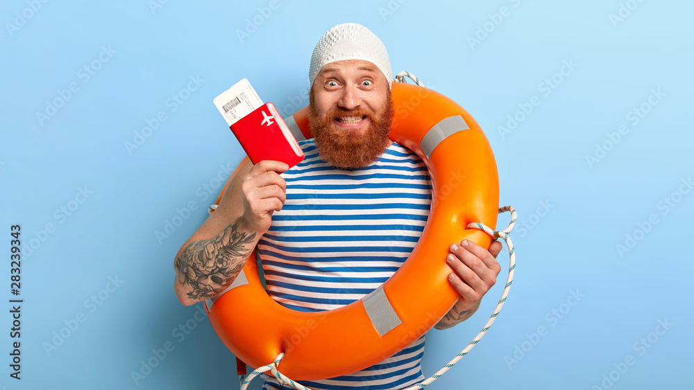 Fototapety, obrazy: Cheerful bearded man holds passport with boarding pass tickets, has summer voyage, dressed in rubber bathingcap and sailor vest, feels excited about future trip, poses indoor. Traveling concept