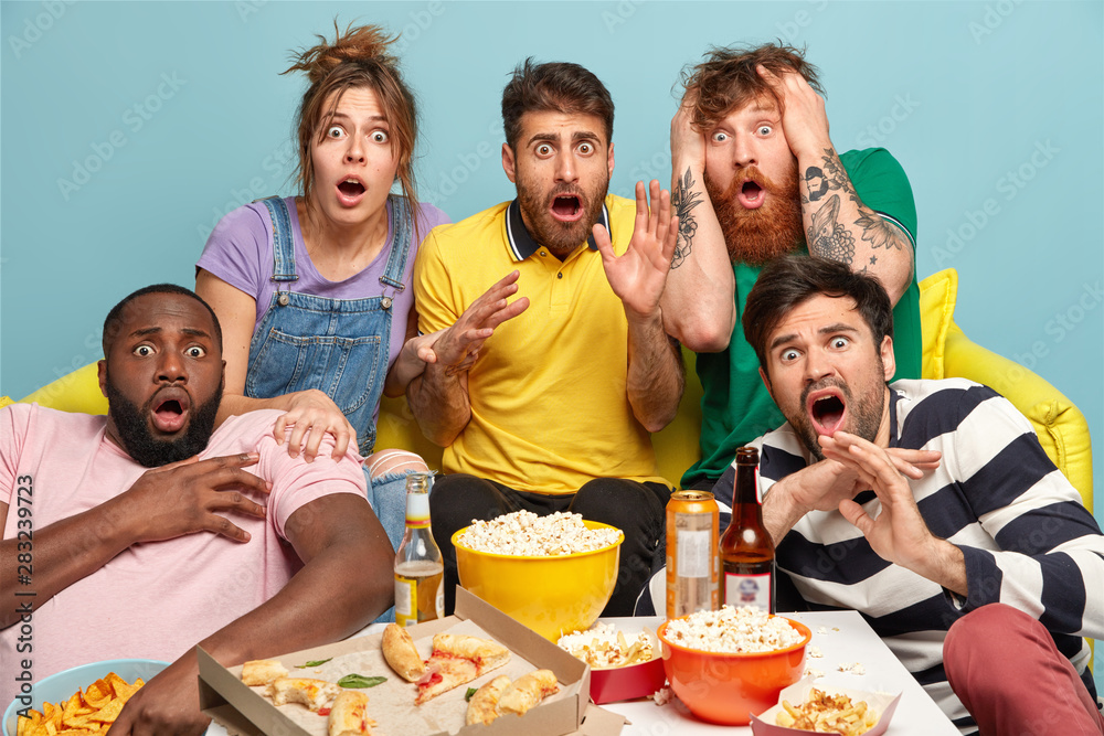 Fototapety, obrazy: Scared group of friends watch horror movie, feel great fear and surprise during thrilled scary film moment, have bated breath, eat junk food, spend lazy day off together sit on couch against blue wall
