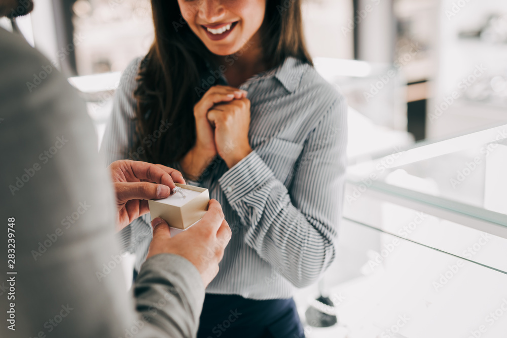 Fototapeta Man buying a ring to his girlfriend in a modern jewelry store.