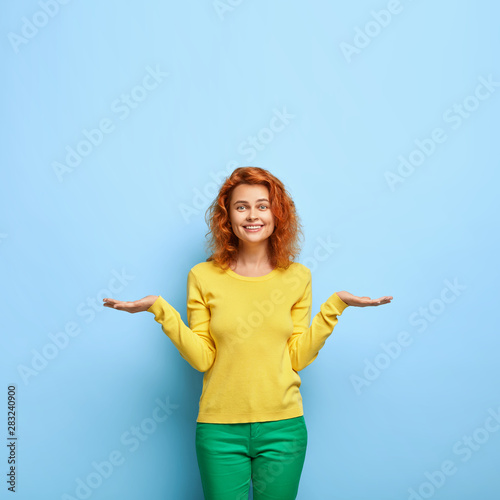Valokuva  Pleased positive European woman with ginger hairstyle raises two palms as if hol