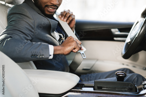 Photo  Business man fastening seat belt in car