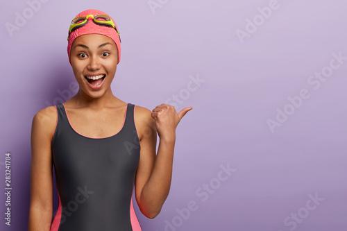Fotografia Joyful dark skinned female swimmer wears bathingcap, black swimsuit, smiles broa