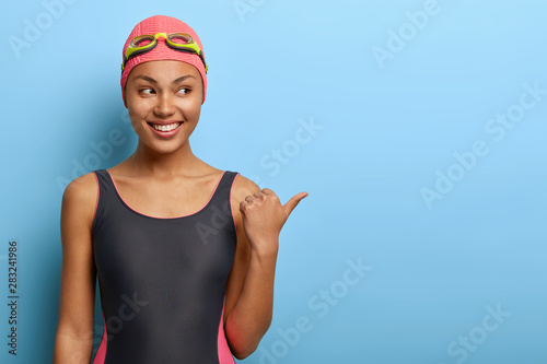 Photo  Professional female swimmer points away on blank space, wears pink swimcap and bathing suit, attracts your attention to awesome promo, has clean skin, healthy body and slim figure