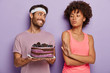 canvas print picture - Will powered dark skinned female refuses to consume delicious cake on plate, makes refusal gesture, says I am against of eating junk food containing fat. Smiling friendly man treats woman with dessert