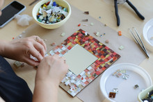 Process Of Making A Mosaic Picture From Ceramic Tile. The Man Organizes With A Tweezers A Puzzle Of Ceramic Elements To Build A Picture.