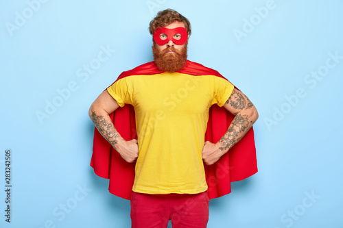 Obraz na plátně Photo of serious male in superhero costume, keeps hands on waist, possesses extraordinary talents, ready to protect our universe, isolated on blue wall