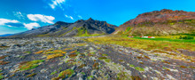 Typical View Of Iceland  Rocky Lava Plains, Covered By Moss And  Mountains At Background.