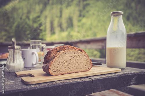 Rustic breakfast on an alpine hut: fresh crisp bread and milk in glass bottle, o Canvas-taulu