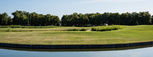 Panoramic Shot Of Green Grass And Trees Near Pond And Blue Sky