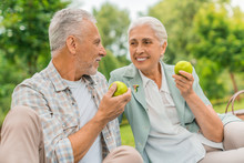 Portrait Of Beautiful Senior Couple Sitting On Blanket Outdoor Eating Apples And Enjoying Time Together