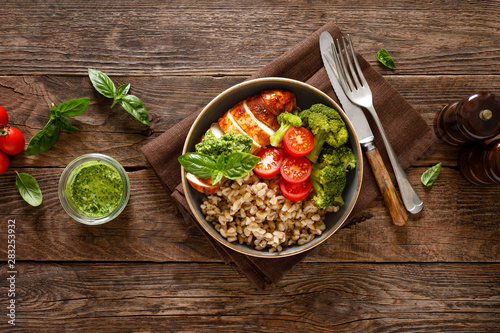 Chicken lunch bowl with broccoli, fresh tomato, pearl barley porridge and basil pesto on wooden rustic background