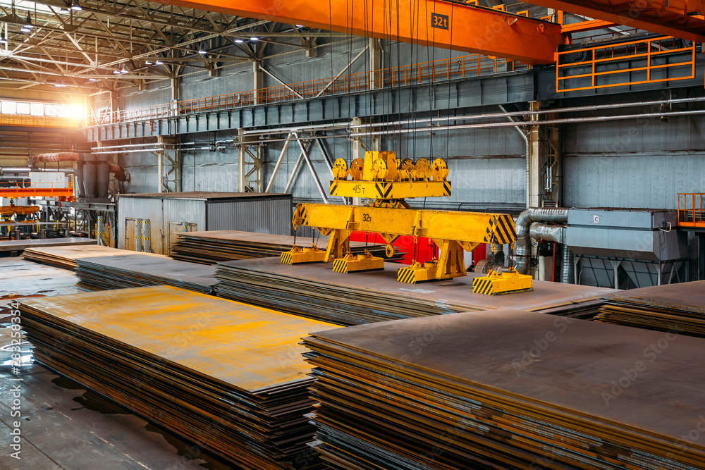 Fototapety, obrazy: Overhead crane with electromagnetic beam grippers lifting steel sheets