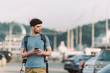 handsome man in t-shirt holding smartphone and looking away