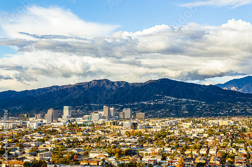 Fototapeta panaramic view of city businesses and homes with hillside homes and mountains wi
