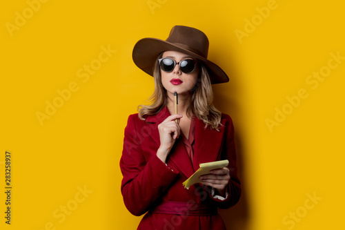 Fotografia  Woman in sunglasses with notebook and pen
