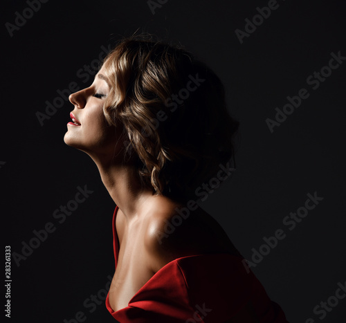 Beautiful trendy woman with curly hair and emotions in red dress posing on dark Fototapeta