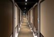 Cabins line narrow hallway in Japanese capsule hotel