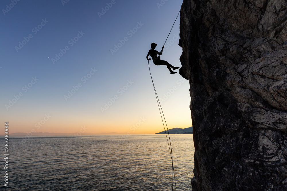 Fototapety, obrazy: Silhouette of a Unrecognizable man rappelling down a steep cliff on the rocly ocean coast during a sunny summer sunset. Taken in Lighthouse Park, West Vancouver, British Columbia, Canada.