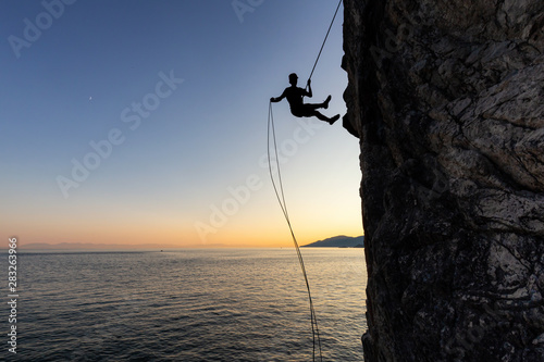 Photo  Silhouette of a Unrecognizable man rappelling down a steep cliff on the rocly ocean coast during a sunny summer sunset