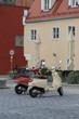 Zwei alte Motorroller auf dem Platz vor farblich passenden Häusern