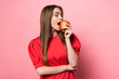 attractive young woman eating apple with closed eyes on pink