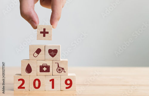 Obraz na plátně  Hand arranging wood block stacking with icon healthcare medical, Insurance for y