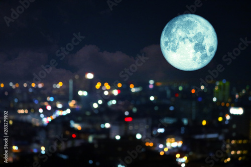 Photo super super full harvest moon on night sky and reflection light of city on windo