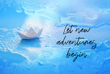 Let New Adventures Begin - Inspiration Quote. Little White Paper Boat Over Blue Background. Travel Concept. Folded Origami Paper Boat On Water. Shallow Depth, Soft Selective Focus.