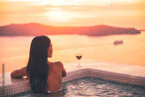 Leinwand Poster Santorini hot tub jacuzzi pool woman - wellness spa concept in luxury retreat - high end fancy lifestyle honeymoon destination