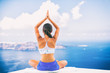 Woman doing yoga meditation in morning sunshine nature landscape- relaxing in beach background.