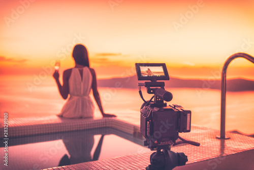 Fotografie, Obraz  Videography behind the scene video camera shooting movie at sunset beach resort hotel filming actress woman acting, luxury travel