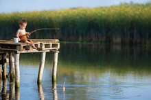 Little Boy Fishing On The Lake