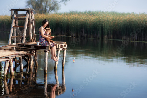Fototapeta little boy with mother fishing on the lake